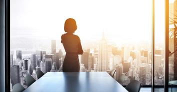 Woman looking over skyline in office hero