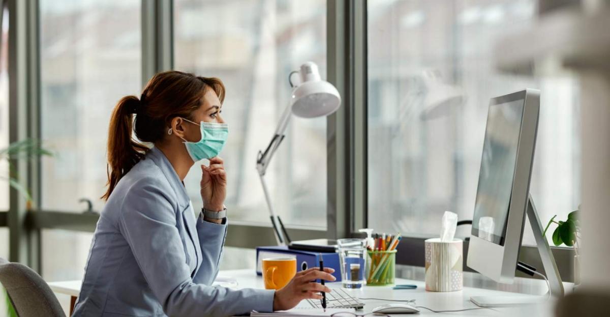 Woman in mask at desk hero